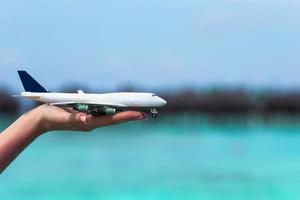 Nahaufnahme einer Hand, die ein Spielzeugflugzeug hält foto