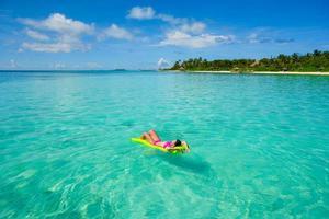 Frau, die auf Floaty am Strand entspannt foto