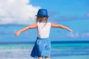 Mädchen mit offenen Armen am Strand foto
