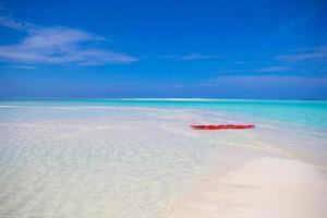 rotes Surfbrett am weißen Sandstrand