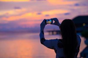Frau, die ein Foto eines Sonnenuntergangs macht