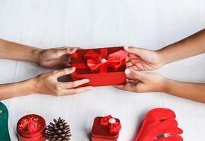 zwei Leute, die ein Geschenk halten foto