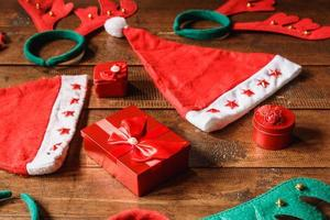 rote Geschenkbox und Weihnachtsmütze auf hölzernem Hintergrund