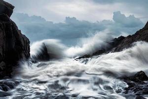 große Welle trifft die Felsen im Sturm