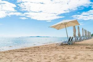 Sonnenschirm und Stühle am wunderschönen tropischen Strand und Meer