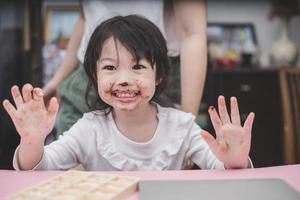 glückliches süßes Mädchen mit einer Schokolade auf ihrem Gesicht