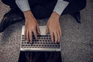 Geschäftsmann, der mit Laptop auf dem Boden arbeitet