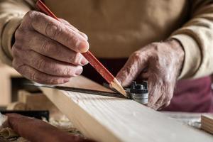 Zimmermann misst eine Planke mit einem roten Stift und einem Metalllineal