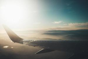 Flugzeugflügel über nebligen Bergen