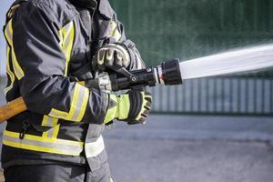 Feuerwehrleute benutzen einen Schlauch