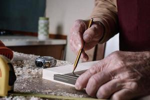 Zimmermann macht Messungen auf einem Tisch