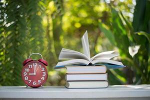 roter Wecker mit Buch auf Naturgartenhintergrund