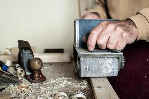 Zimmermann, der Werkstückverarbeitung auf hellbraunem Holztisch tut