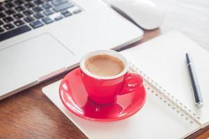 Kaffeetasse und Stift auf einem Notizblock vor einem Laptop