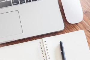 Nahaufnahme eines Notizbuchs mit einem Stift und einem Laptop foto