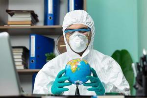 Person im Schutzanzug hält Globus Erde mit Hand im Büro