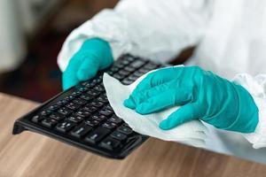 Person mit Schutzausrüstung, die eine Computertastatur reinigt foto