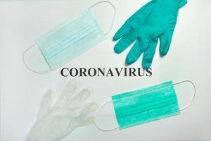 medizinische Schutzmasken mit Handschuhen auf dem Tisch mit Coronavirus-Wort foto