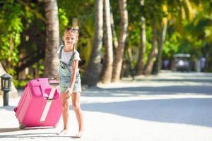 Mädchen zieht rosa Gepäck foto