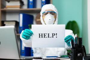 Person im Schutzanzug hält Hilfewort im Büro foto