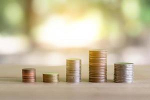 Stapel Münzen auf Holztisch mit Bokeh-Hintergrund