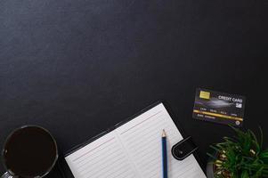 Notizbuch und Kreditkarte auf schwarzem Hintergrund foto