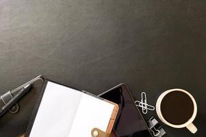 schwarzer Schreibtisch mit Kaffee und Bürowerkzeugen