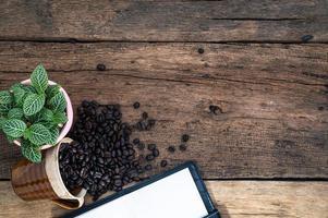 Holzschreibtisch mit Notizbuch und Kaffeebohnen