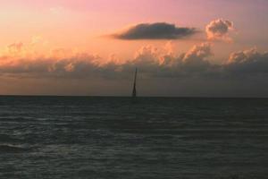 dunkler Ozean unter einem orangefarbenen Himmel foto