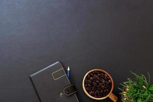 schwarzer Schreibtisch mit Kaffeebohnen und Notizbuch