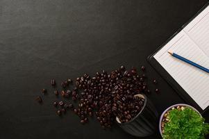 schwarzer Schreibtisch mit Notizbuch und Kaffeebohnen