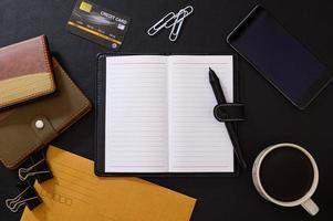 schwarzer Schreibtisch mit Kaffee und Büromaterial foto