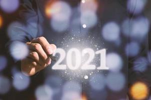 menschliche Hand und 2021 Zeichen für das neue Jahr