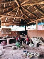 Menschen sitzen auf braunen Holzstühlen in Peru