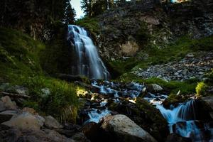 Sonnenschein auf einem dunklen Wasserfall foto