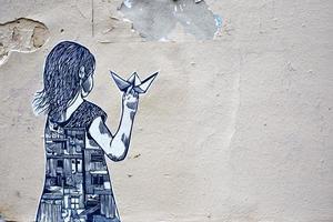Montmartre, Frankreich, 2020 - Straßenkunst eines Mädchens, das ein Papierboot hält foto