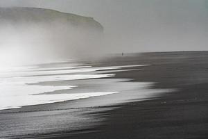 schwarzes Strandufer mit Nebel