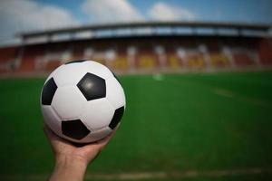 Hand, die einen Fußball auf Gras mit Stadionhintergrund hält