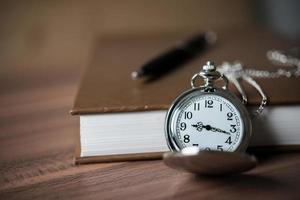 Nahaufnahme einer goldenen Taschenuhr und eines Buches