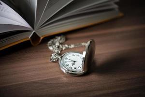 Nahaufnahme einer goldenen Taschenuhr und eines Buches foto