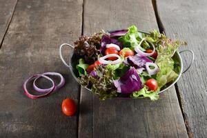 frischer Gemüsesalat mit rustikalem altem hölzernem Hintergrund foto