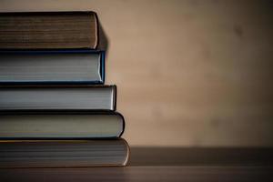 Stapel Bücher auf Holztisch.