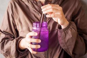 Person, die ein lila Glas hält