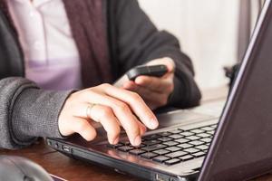 Person, die an einem Laptop arbeitet, während sie ihr Telefon betrachtet