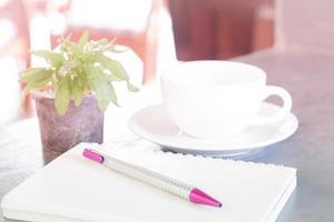 Notizbuch mit Kaffee und Pflanze foto