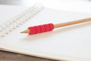 Nahaufnahme eines roten Bleistifts auf einem Notizbuch