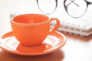 Nahaufnahme einer Kaffeetasse mit einem Notizbuch und einer Brille