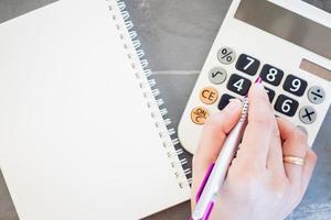 Hand hält einen Stift, der Zahlen auf einem Taschenrechner stanzt foto