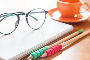 Bleistifte mit Brille auf einem Notizbuch mit einer Kaffeetasse foto