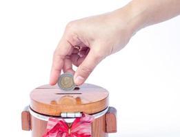 Nahaufnahme einer Hand, die eine Münze in eine Sparbüchse legt